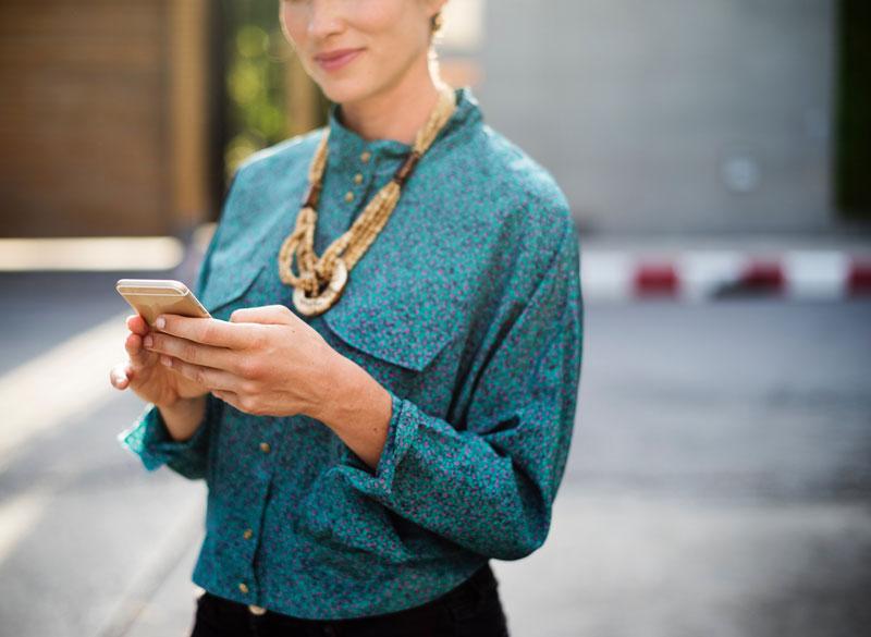 Une femme élégante consulte son mobile dans la rue