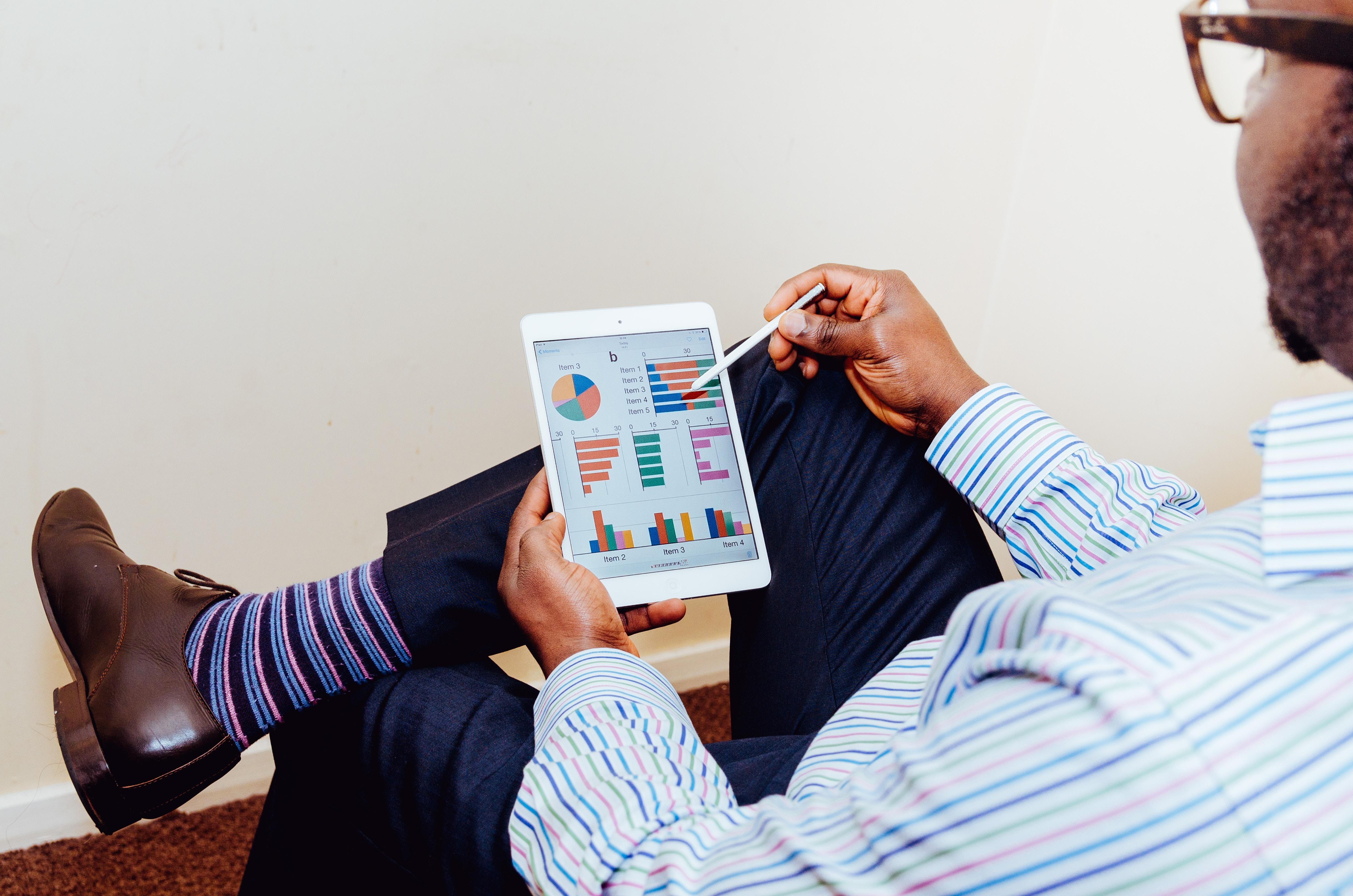 Un homme noir regardant des diagrammes sur sa tablette